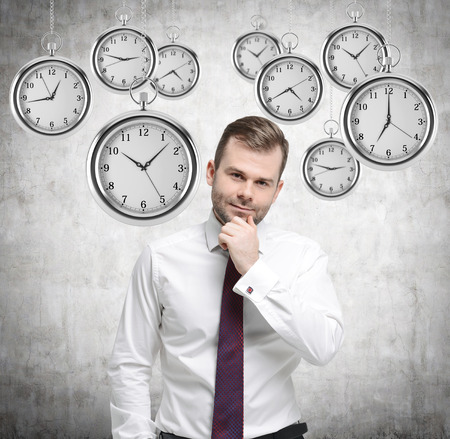 streamlining: A thinking handsome businessman is holding his own chin. Several models of pocket watches are hovering in the air. A concept of a value of time in business. Concrete background. Stock Photo