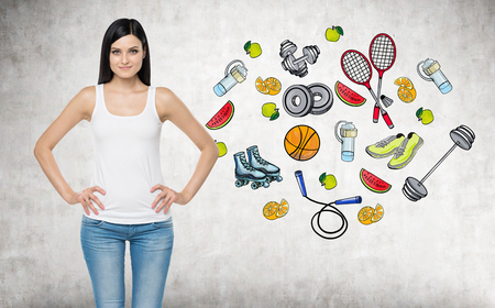 favour: A beautiful brunette lady who is trying to make a choice in favour of a certain sport activity. Colourful sport icons are drawn on the concrete wall. A concept of a healthy lifestyle. Stock Photo