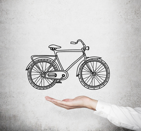 nonpolluting: A hand in formal white shirt holds a model of a sketched bicycle. Concrete wall on background. A concept of commuting or travelling. Stock Photo