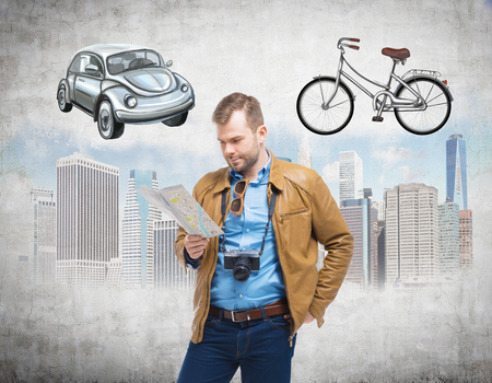 disadvantages: A handsome man in casual clothes holds a map and thinks about the most suitable way for travelling or commuting in the city. Sketches of a car, a bicycle and New York city are on the concrete background. Stock Photo