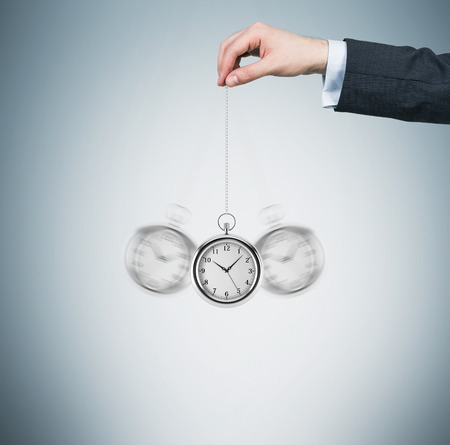 timekeeping: A hand holds a pocket watch in a chain as a pendulum. Light blue background. Time is money concept.
