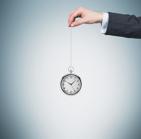timekeeping: A hand holds a pocket watch in a chain. Light blue background. Time is money concept. Stock Photo