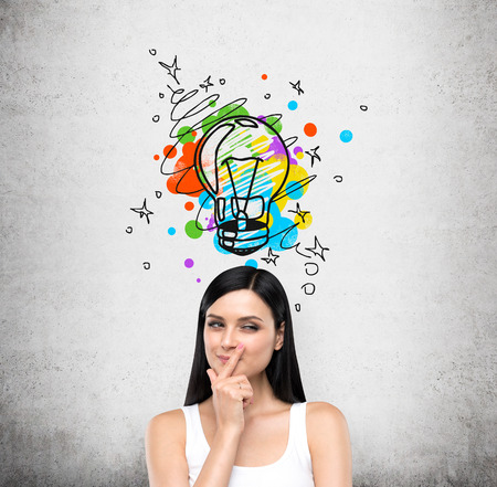 case: A portrait of a young artful brunette lady who is trying to create a new idea for some business project or case study. A colourful lightbulb as a concept of a new idea is drawn on the concrete wall. Stock Photo