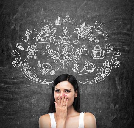 matrimonio feliz: Un retrato de una dama morena feliz en una camiseta blanca que está cubriendo su boca con la mano y soñando con ir de compras. Iconos de las compras se dibujan en la pizarra negro.