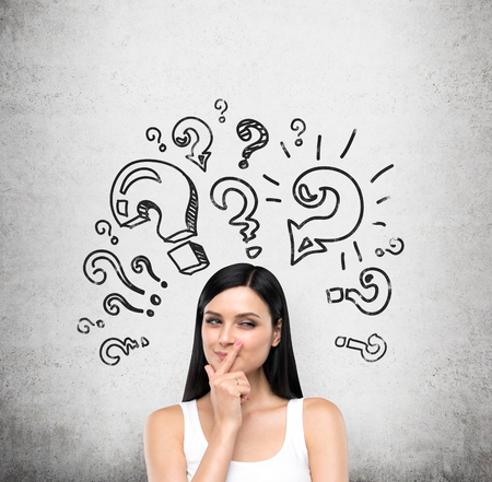 artful: A portrait of a young artful brunette lady who is trying to find out a solution of some problem. The lady is in a white tank top. Different shapes of question marks are drawn on the concrete wall.