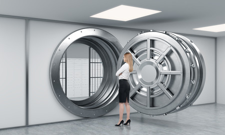 depository: young lady standing in front of a big unlocked round metal safe in a bank depository with her back half turned,  a concept of security and client service