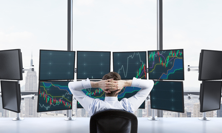 wallstreet: man with hands locked on back of the head sitting in front of monitors, processing data for trading, window at the background, new york