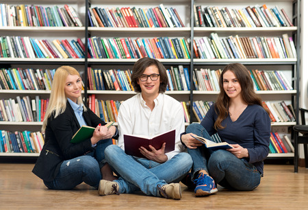 legs open: two smiling young girls and smiling young man sitting on the floor in the library with legs crossed each reading an open book in their hands, bookshelves at the background, a concept of reading