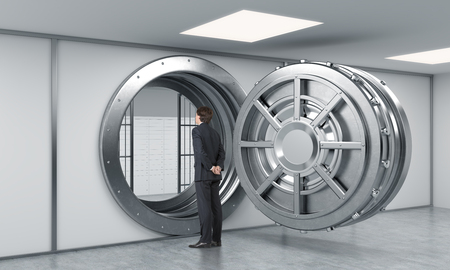 security man: young man standing in front of a big unlocked round metal safe in a bank with lock-boxes inside in a depository with his back half turned looking inside,  a concept of security and aspirations Stock Photo