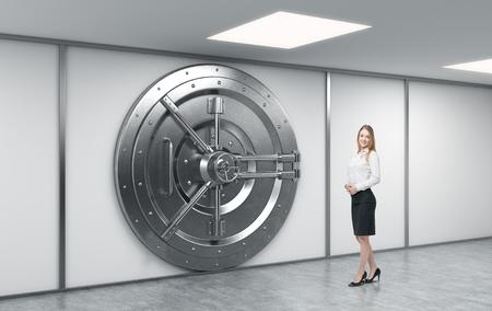 caja fuerte: trabajador del banco de pie en frente de un gran redondo de metal caja fuerte cerrada en un dep�sito bancario, un concepto de seguridad y servicio al cliente Foto de archivo