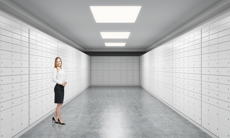 depository: A beautiful private manger of a bank is standing in a room with safe deposit boxes. A concept of storing of important documents or valuables in a safe and secure environment. Stock Photo