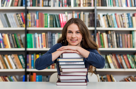 industrious: smiling young girl sitting at a desk in the library with her arms on a big pile of books and chin on them, looking in front of her, thinking,  a concept of knowledge, blurred books at the background