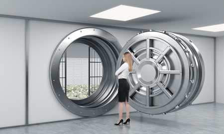lockbox: young lady standing in front of a big unlocked round metal safe full of money in a bank depository with her back half turned,  a concept of security and wealth Stock Photo