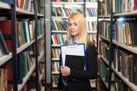 copy book: young lady with blond hair standing and holding a black copy book and a note pad between book shelves in the library, looking in front of her, slight turned, a concept of studying