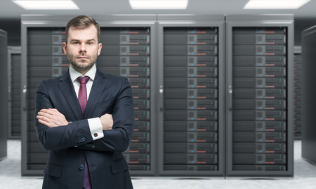 data processing: young man standing with hands crossed in front of server for data storage, processing and analysis, rows of machines at work, front view, blurred background