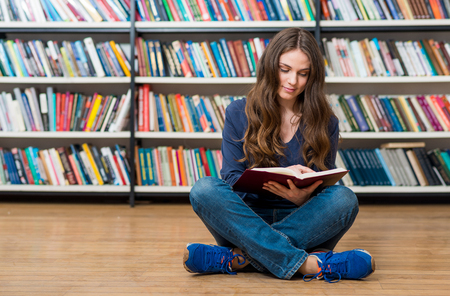girl studying: smiling young girl sitting on the floor in the library with crossed legs, with an open book on her knees looking into the book, blurred book shelves at the back, a concept of studying