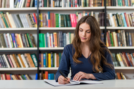 knowledgeable: serious young girl with loose long dark hair  sitting at a desk in the library with an open note book writing, looking at notes, a concept of studying, blurred books at the back