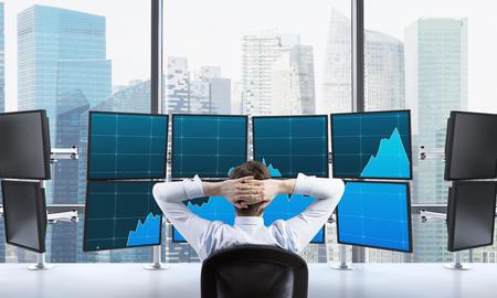 efectivo: hombre con las manos bloqueado en la parte posterior de la cabeza que se sienta delante de los monitores, el procesamiento de datos para el comercio, Singapur en el fondo