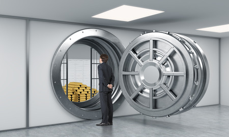 client service: young man standing in front of a big unlocked round metal safe in a bank with a pyramid of gold bars and lock-boxes inside, a concept of security and client service depository.