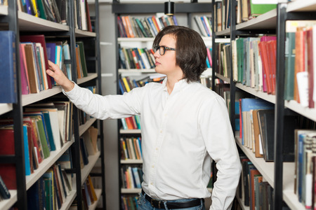 alumni: young man with dark hair choosing a book standing between shelves in the library, touching a book, side view, a concept of studying and choice