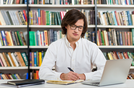 man with glasses: serious young man with dark hair sitting at a desk in the library making notes, laptop and organiser on the table, looking at notes, a concept of studying, blurred books at the back Stock Photo