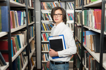 copy book: young man with dark hair standing and holding a black copy book and a note pad between book shelves in the library, looking in front of him, slightly turned, a concept of studying Stock Photo