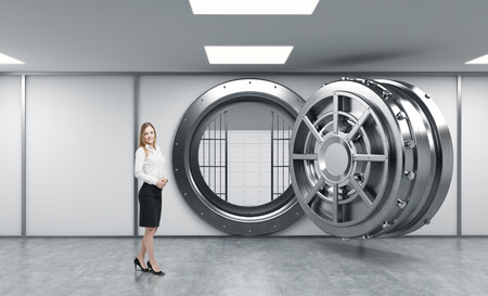 lockbox: smiling young lady standing in front of a big unlocked round metal safe in a bank depository with lock-boxes inside,  a concept of trust and client service