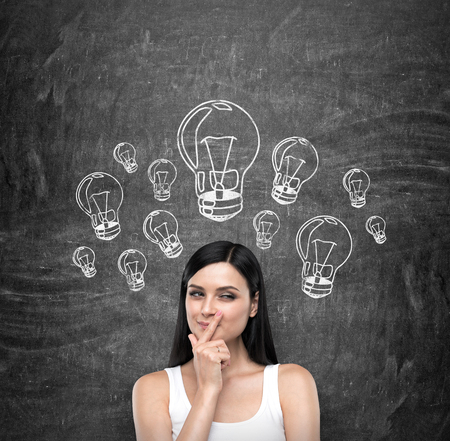 quizzical: A portrait of a young artful brunette lady who is trying to create a new ideas for some business project or case study. A range of lightbulbs as a concept of new ideas are drawn on the black chalkboard. Stock Photo