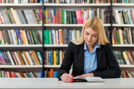 alumni: young girl with blonde hair  sitting at a desk in the library with an open book reading, looking down, a concept of knowledge aquisition, blurred books at the back