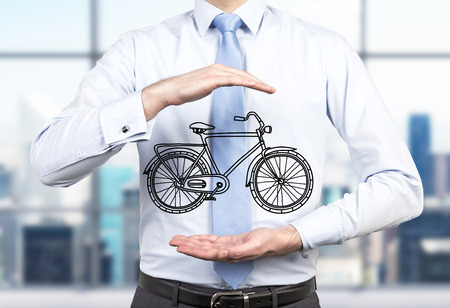 managerial: A person in formal clothes holds a sketched bicycle between his hands. A modern panoramic office in blur is on the background. A concept of environmental friendly ways of commuting and travelling.