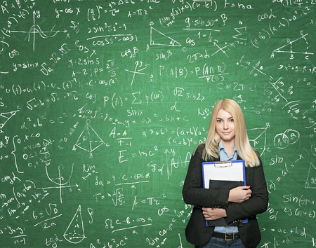 alumni: a young girl standing and holding note books, green blackboard with small signs and dawings at the background, a concept of studying