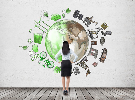 woman in front of the wall thinking about oil production and pollution, brown illustration of oil industry and green eco energy on white wall arranged in circle, concept of environment, back view Stock Photo