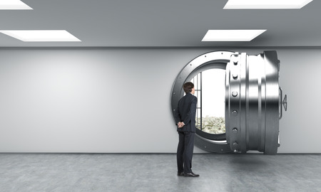robbing: young man standing in front of a big unlocked round metal safe in a bank with heaps of dollars inside, in a depository, with his back half turned looking inside,  a concept of aspirations