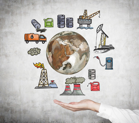 hand as if holding an illustration of oil industry components from extraction to petroleum stations on a concrete wall, polluted earth in the centre, a concept of pollution Stock Photo