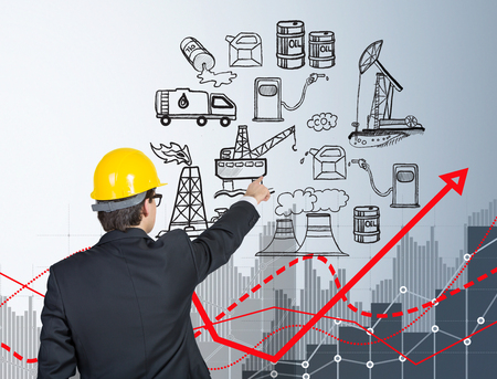 oil pollution: man standing and pointing at the illustration of oil production components on white wall,  back view, red graph of oil pollution, concept of environmental pollution Stock Photo