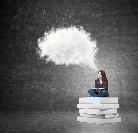 book concept: young woman sitting on a pile of books with an open book on her knees thinking about future or looking for a solution of a problem, black wall at the background with a white cloud of thoughts, concept of dreaming Stock Photo