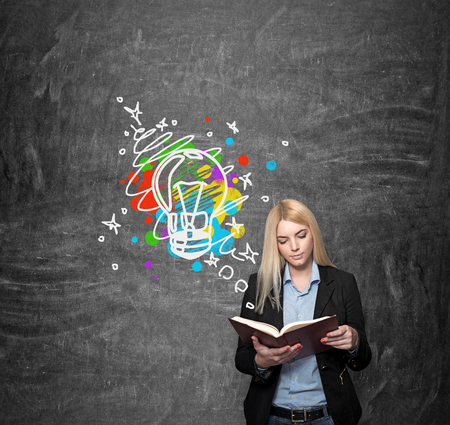 alumni: a young girl standing at a wall reading a book, blackboard with a coloured image at the background, a concept of choice and studying