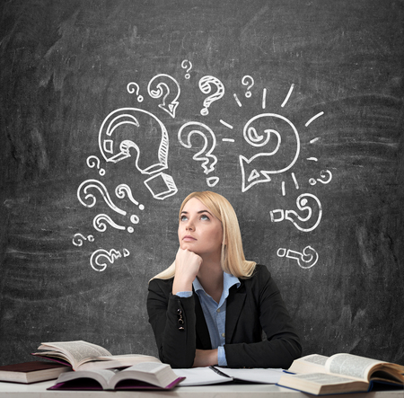 yearning: Young beautiful woman sitting at the desk with books on it and thinking educationl. Drawn question marks over the blackboard. Concept of education and choice Stock Photo