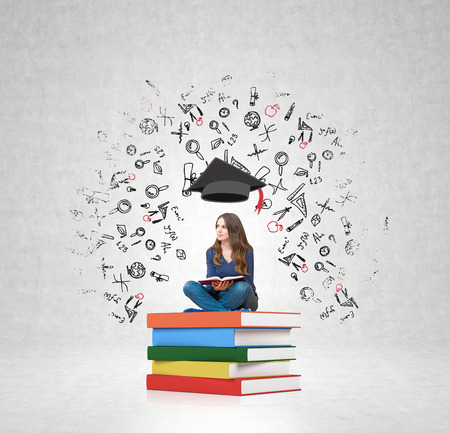 young woman sitting: young woman sitting on a pile of books with an open book on her knees thinking about future, square academic hat above her head, white wall with illustrations at the background, concept of education choice Stock Photo