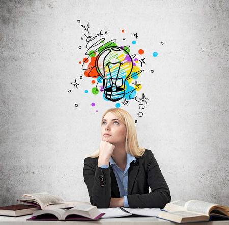 yearning: Young beautiful woman sitting at the desk with books on it and thinking educationl. Drawn coloured splash and a bulb  over the concrete wall. Concept of choice