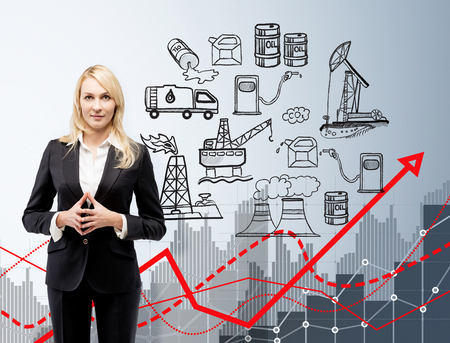 oil pollution: woman standing, front view, illustration of oil production components on white wall, red graph of oil pollution, concept of environmental pollution Stock Photo