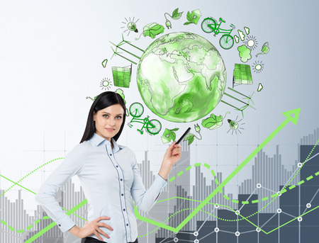 energy production: woman standing and pointing at the illustration of eco energy production on white wall behind, green graph of ecological improvement, front view, concept of clean environment Stock Photo
