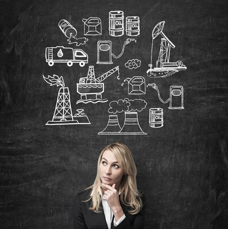 monopoly: a woman standing in front of the wall with hand to the chin thinking about oil industry, illustration of oil industry components on a black wall, concept of pollution Stock Photo