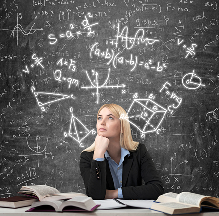 yearning: Young beautiful woman sitting at the desk with books on it and thinking educationl. Drawn science icons over the blackboard. Concept of education and choice
