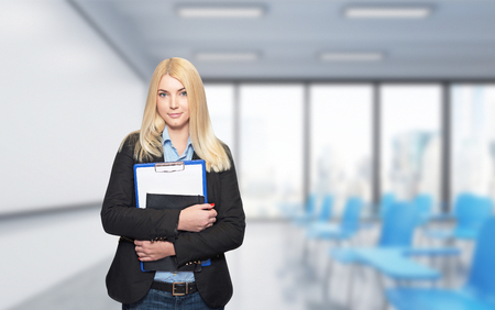 alumni: a young girl standing at a wall holding note books, isolated, blurred lecture hall with alackboard and blue chairs at the background, a concept of studying