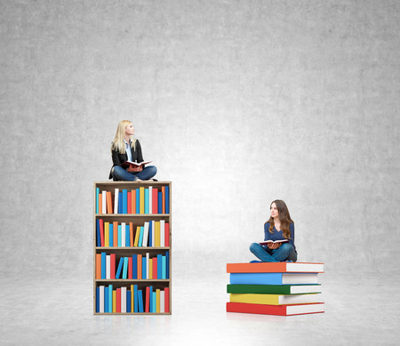 professional development: young woman sitting on a pile of books with an open book on her knees and young woman sitting on a bookcase with an open book on her knees thinking about future, white wall at the background, concept of dreaming