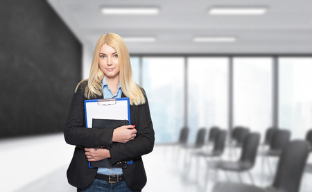 alumni: a young girl standing at a wall holding note books, isolated, blurred lecture hall with alackboard and chairs at the background, a concept of studying Stock Photo