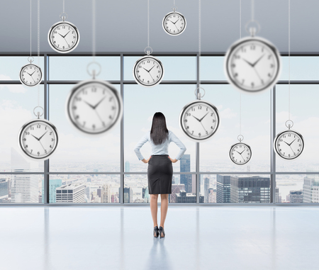 streamlining: Businesswoman standing and looking into the window, back view, several models of pocket watches hovering in the air. A concept of a value of time in business. New York panoramic view. Stock Photo