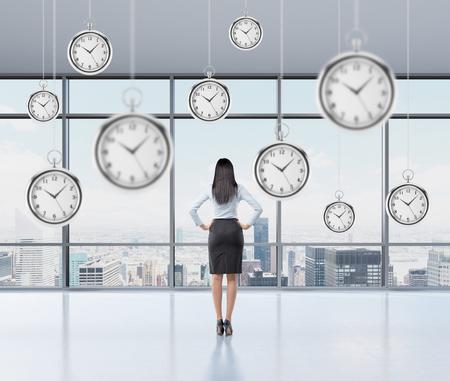 valor: Empresaria de pie y mirando hacia la ventana, vista posterior, varios modelos de relojes de bolsillo flotando en el aire. Un concepto de un valor de tiempo en el negocio. Nueva York vista panor�mica. Foto de archivo
