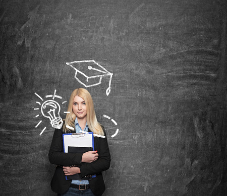 a young girl standing at a wall holding note books, blackboard with a square academic hat at the background, a concept of planning and studying